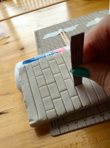Score the brick lines with a credit card or metal ruler, and the short lines with a thin strip of credit card
